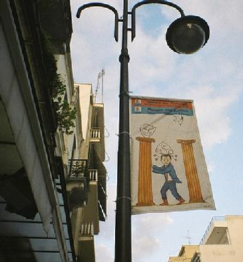 Political cartoon, public banner, Patras, Greece.